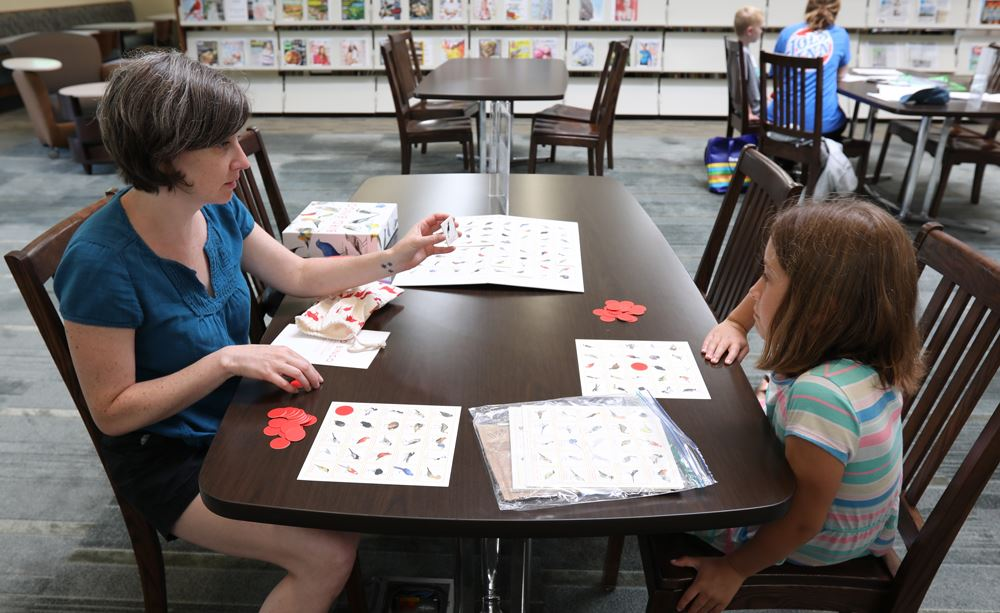 woman shows flashcard to child at a table in the library